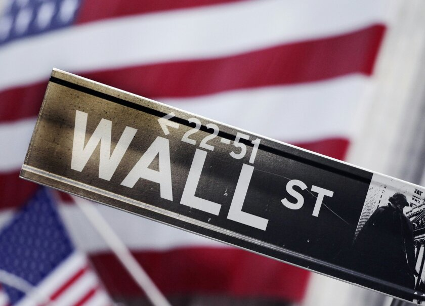 FILE - This Aug. 9, 2011, file photo, shows a Wall Street street sign near the New York Stock Exchange, in New York. A strong jobs report pushed up the stock market higher Thursday, July 3, 2014, with the Dow Jones industrial average crossing 17,000 for the first time. The Department of Labor said