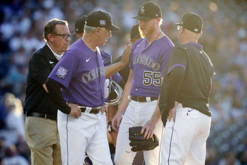Colorado Rockies manager Bud Black, front left, pats starting pitcher Jon Gray (55) who is pulled from the mound as pitching coach Steve Foster, right, looks on in the third inning of a baseball game against the Oakland Athletics Friday, June 4, 2021, in Denver. (AP Photo/David Zalubowski)