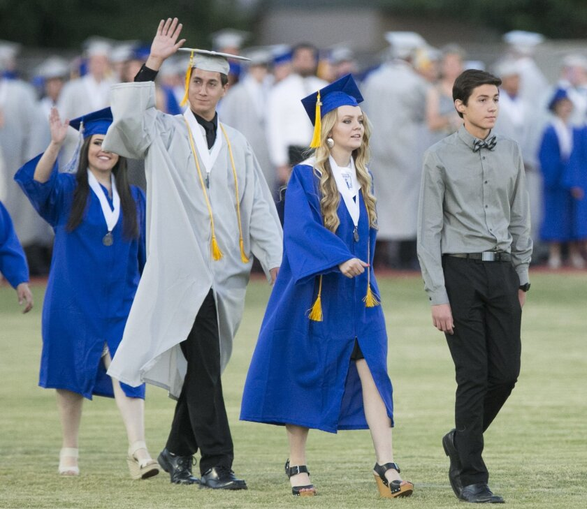 In this photo taken, Thursday evening, May 26, 2016, Stephen Dwyer, right, who could not wear a cap and gown nor sit with his classmates, leads graduates during the Dobson High School graduation in Mesa Ariz. Dwyer, who withdrew from classes his junior year to receive a lifesaving bone-marrow transplant to treat high-risk leukemia, returned for classes his senior year and he worked to catch. He is only 2.5 credits short of meeting the requirements to graduate from Dobson. He expects to graduate in December. The school and the Mesa Public Schools district officials said Dwyer may not wear his cap and gown, but can lead the Class of 2016 out at the beginning of the ceremony.(David Wallace/The Arizona Republic via AP) MARICOPA COUNTY OUT; MAGS OUT; NO SALES; MANDATORY CREDIT