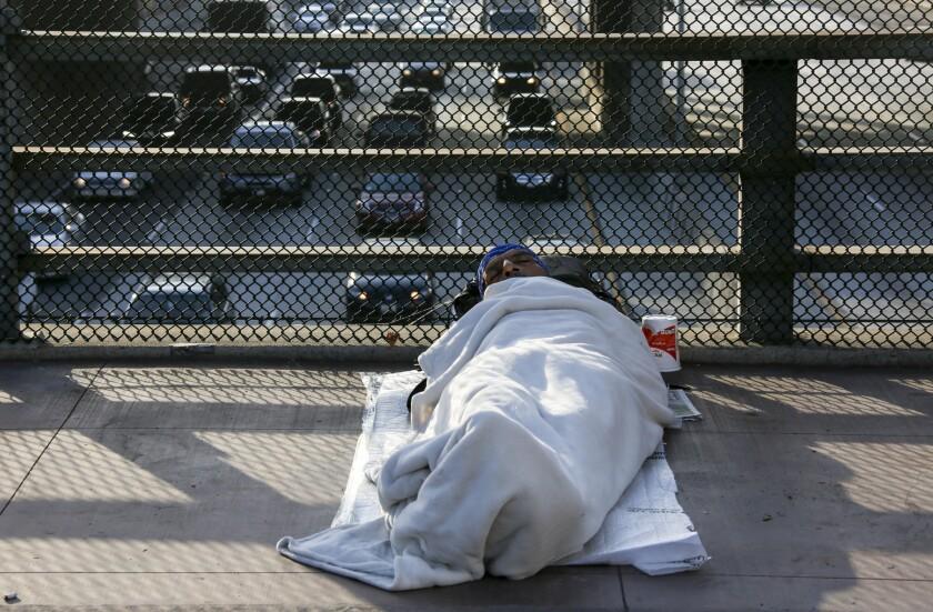A homeless man sleeps on Main Street bridge in downtown Los Angeles.
