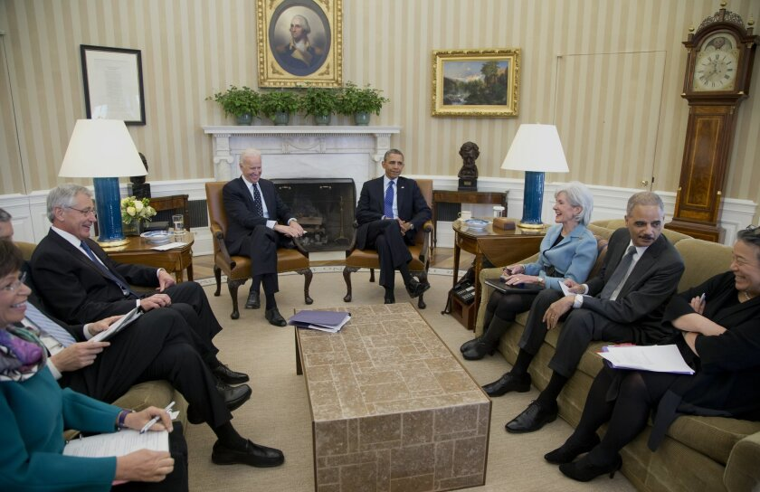 President Barack Obama and Vice President Joe Biden, center, meet with, from left, White House Senior Adviser Valerie Jarrett, Education Secretary Arne Duncan, Defense Secretary Chuck Hagel, Health and Human Services Secretary Kathleen Sebelius, Attorney General Eric Holder, and Executive Director of the White House Council on Women and Girls, Tina Tchen, who is also the Director of the White House Office of Public Engagement, in the Oval Office of the White House in Washington, Wednesday, Jan. 22, 2014, to discuss the Council on Women and Girls. (AP Photo/Carolyn Kaster)