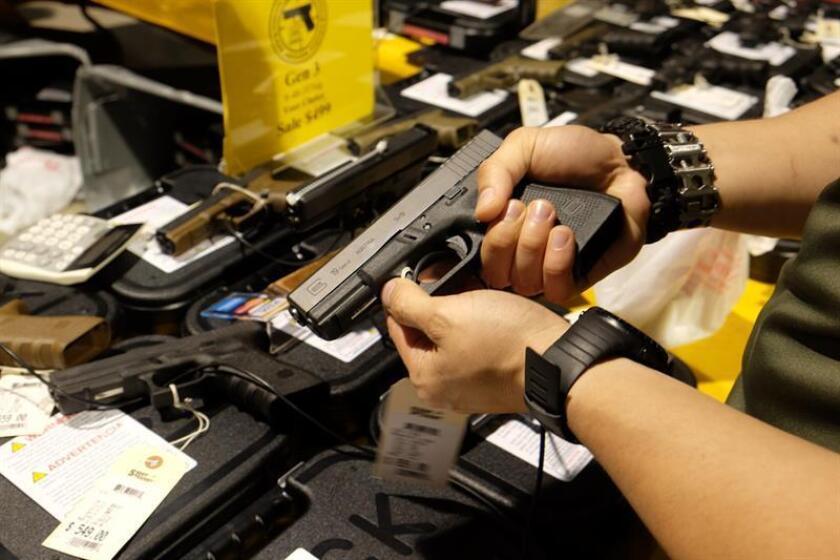 Un hombre sostiene un arma Glock 19 durante la Feria de Armas de Miami. EFE/Archivo
