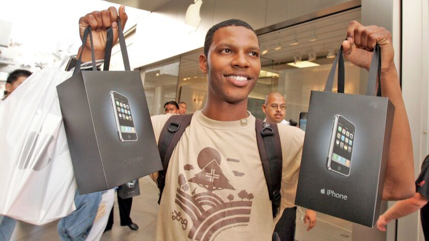 Nathan Alford with the two iPhones he bought for his boss as he leaves the Apple Store at the Westfield Century City on June 29, 2007.
