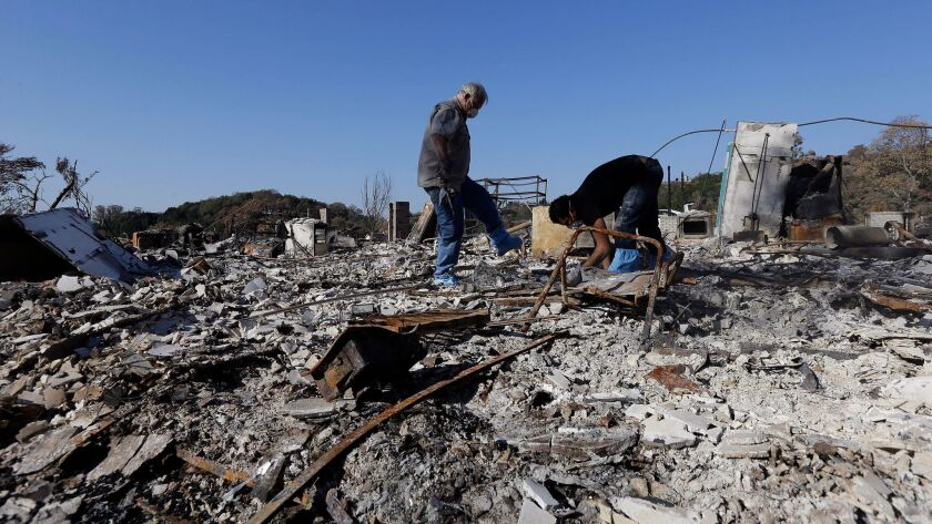 Timothy Lillyquist, left, and Johnny Quirarte on Oct. 31 search through their friend Mary Burns' home that was destroyed by wildfires in Santa Rosa, Calif.