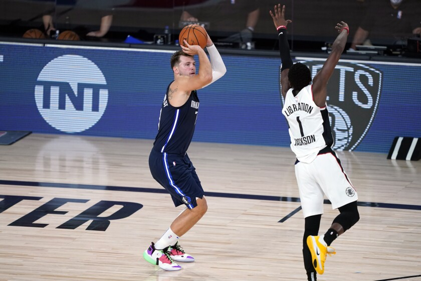 Dallas Mavericks' Luka Doncic (77) shoots his game-winning 3-point basket as Los Angeles Clippers' Reggie Jackson.