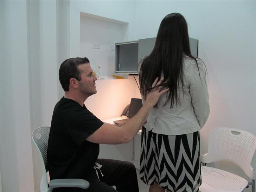 El cirujano ortopeda de columna vertebral Fernando Villamil atiende a una paciente en su consultorio en San Juan, Puerto Rico. EFE/Archivo