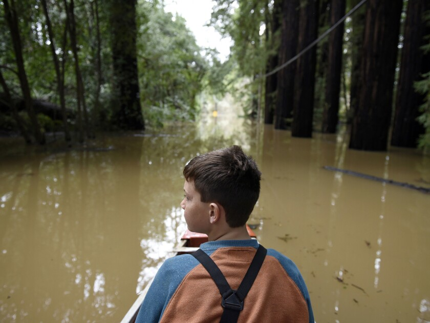 Mathais McCarthy looks around while canoeing down a street flooded by the waters of the Russian Rive
