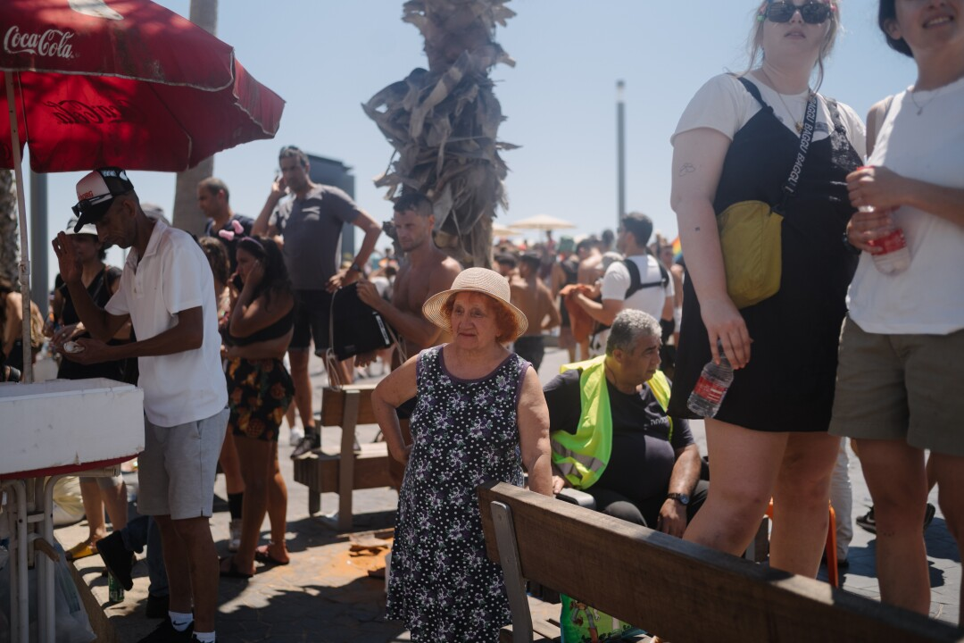 A woman attending the Pride parade pauses to watch people dance.
