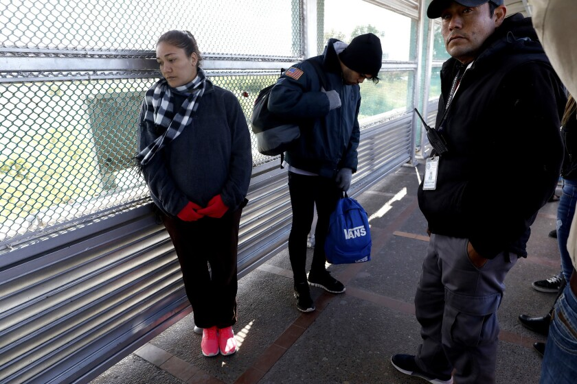 Daimaris Gonzalez, 30, who is pregnant, and Jason, 22, center, both of Cienfuegos, Cuba, at the Gateway International Bridge, as they await being taken into custody by U.S. Customs and Border Protection officers to seek political asylum.