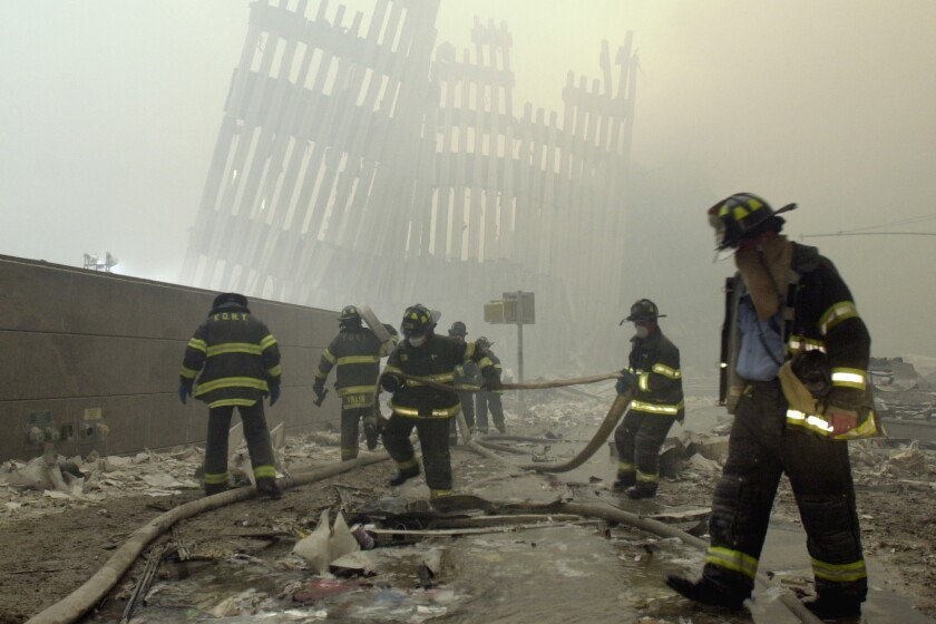 Firefighters work at the World Trade Center towers after the 9/11 terrorist attack in New York in 2001.