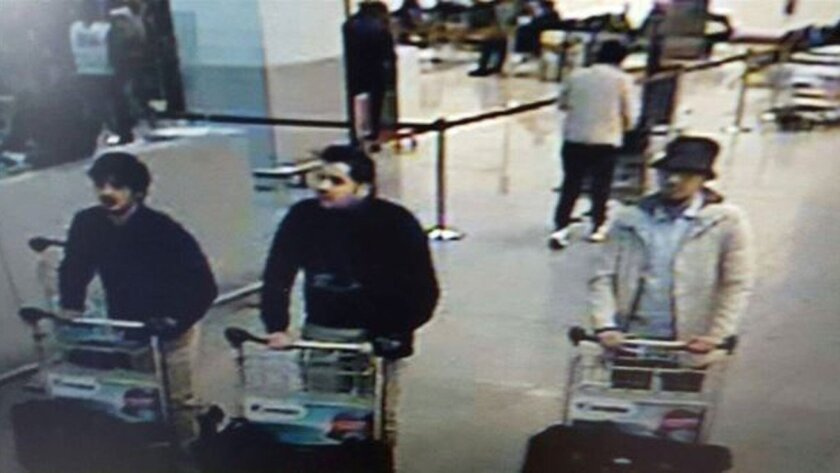 In this image provided by the Belgian Federal Police in Brussels on Tuesday, March 22, 2016 of three men who are suspected of taking part in the attacks at Belgium's Zaventem Airport. The man at right is still being sought by the police and two others in the photo that the police issued were accord