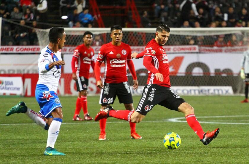 El jugador Guido Rodríguez de los Xolos Tijuana lleva el balón ante el jugador del Puebla, Francisco Torres durante el partido que enfrentó a ambos equipos en la segunda semana del Torneo Clausura 2017 disputado en el estadio Agua Caliente de la ciudad de Tijuana.
