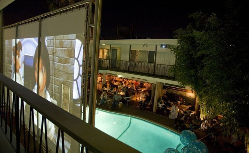 The night scene at the Pearl Hotel: Movie screen, pool, restaurant lounge.