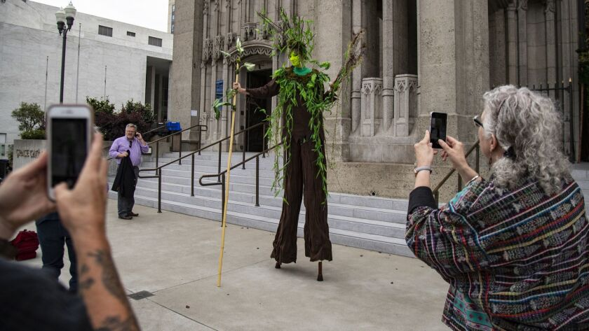 SAN FRANCISCO, CA - SEPTEMBER 12, 2018: A woman on stilts dressed as a tree captures peoples attenti