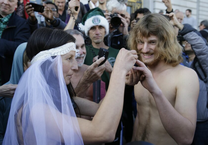 Gypsy Taub, left, places a ring on the finger of Jaymz Smith, right, during their nude wedding outside City Hall, Thursday, Dec. 19, 2013, in San Francisco. Taub, the face of San Francisco's nude rights movement, tied the knot outside City Hall and was later cited and released by police. Taub, a mo