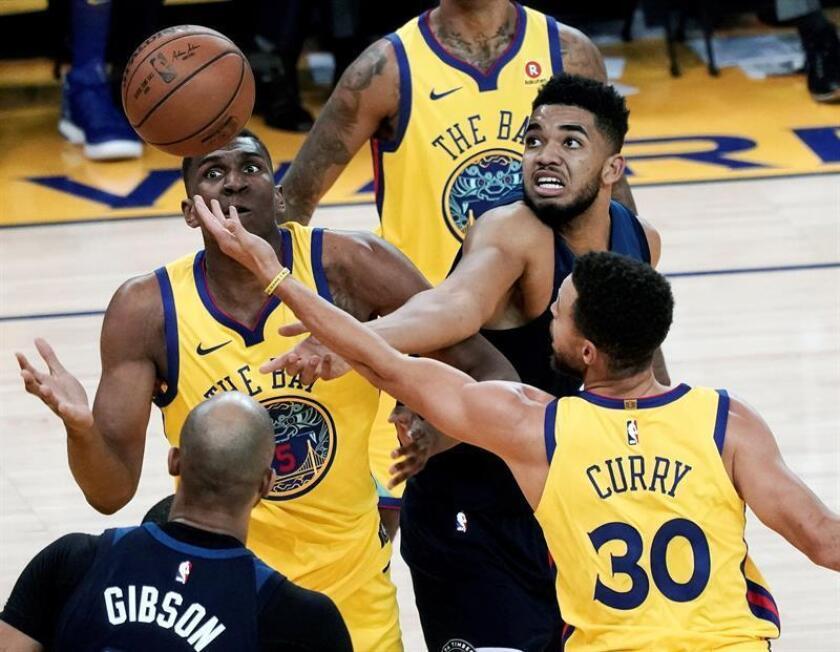 Los jugadores de los Warriors Kevon Looney (i) y Stephen Curry (30) luchan por el balón con Karl-Anthony Towns (d), de los Timberwolves, durante el partido de la NBA que enfrentó a los Tomberwolves de Minnesota y a los Golden State Warriors en el Oracle Arena en Oakland, California, Estados Unidos, el 25 de enero. EFE