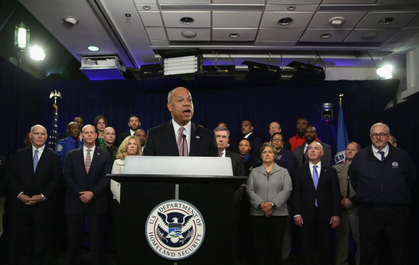 Secretary of Homeland Security Jeh Johnson speaks at a news conference as department employees listen. He said 75% to 80% of his agency's workforce would have to come to work without pay if Congress doesn't fund the department.