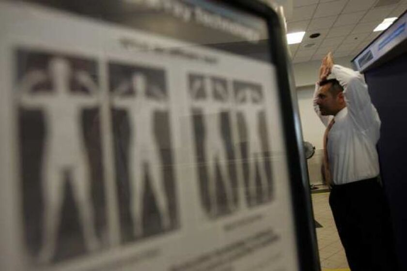 A TSA agent demonstrates the full-body scanner at Los Angeles International Airport.