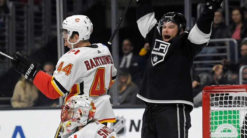 Kings right wing Dustin Brown, right, celebrates a goal by center Anze Kopitar as Calgary Flames defenseman Matt Bartkowski, upper left, and goalie Mike Smith look on during the second period on Oct. 11.
