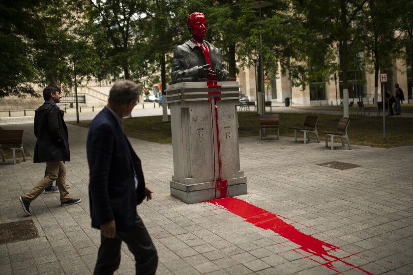 People walk past a bust of former Belgian King Baudouin in Brussels, Friday, June 12, 2020, vandalized as part of anti-racism protests in the country. (AP Photo/Francisco Seco)