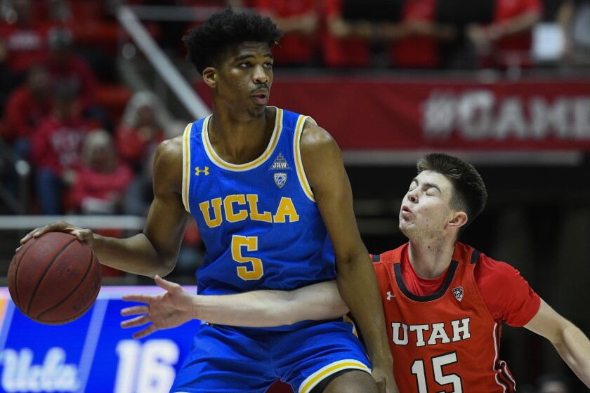 UCLA guard Chris Smith (5) looks to dribble around Utah guard Rylan Jones (15) during the first half of a game Feb. 20 at the Jon M. Hunstman Center.