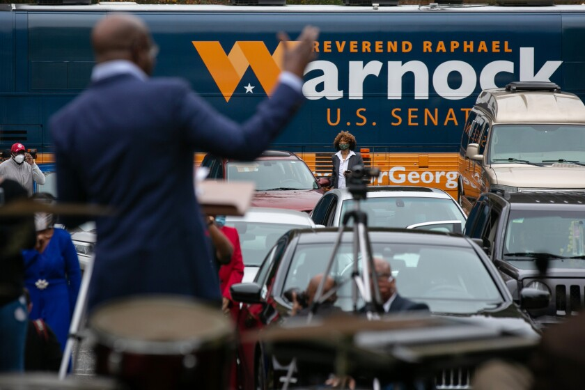 The Rev. Raphael Warnock speaks to churchgoers in and out of their cars at a recent socially distanced drive-in service.