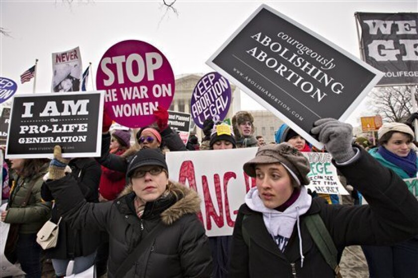 Anti-abortion activists and supporters of legal abortion stand in front of the Supreme Court in Washington, Friday, Jan. 25, 2013, on the 40th anniversary of the Roe v. Wade decision.  Thousands of anti-abortion demonstrators marched through Washington to the steps of the U.S. Supreme Court to prot