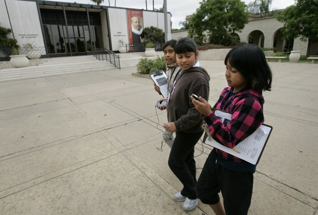 Walking in front of the Timken Museum of Art on Tuesday, Rosa Parks Elementary School students (from left) Odalis Moreno, Yaritzy Nogeron and Nayely Barrientos explore Balboa Park with their smart phones. Peggy Peattie / Union-Tribune photos