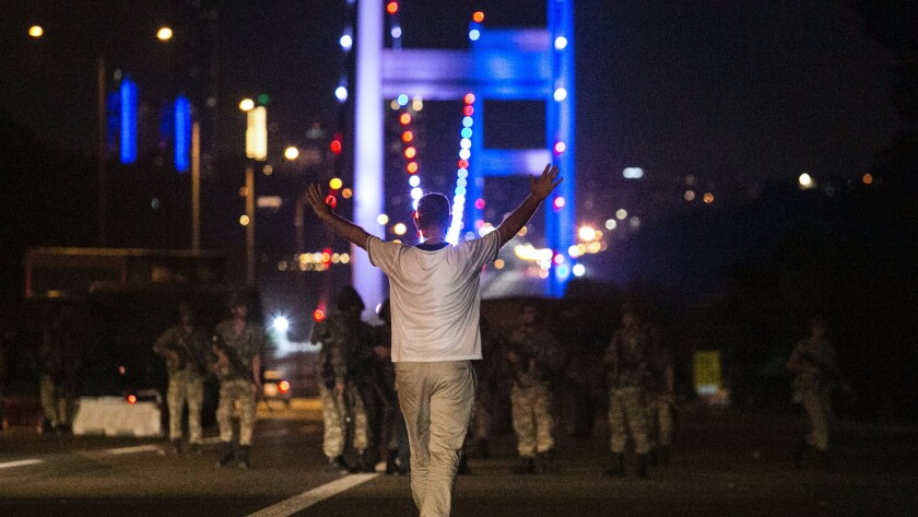 A man approaches Turkish soldiers on the Bosphorus Bridge in Istanbul on July 16, 2016.