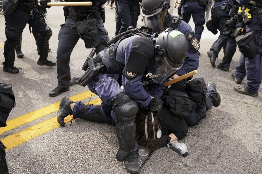 Police detain a protester, Wednesday, in Louisville, Ky.