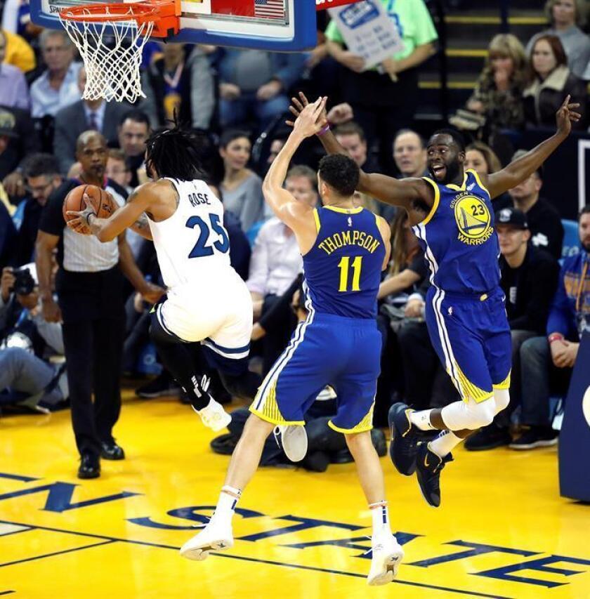 Klay Thompson (c) y Draymond Green (d) de los Golden State Warriors en acción ante Derrick Rose (i) de Minnesota Timberwolves, durante el juego de la NBA entre los Minnesota Timberwolves y los Golden State Warriors en el Oracle Arena en Oakland, California (EE.UU.). EFE