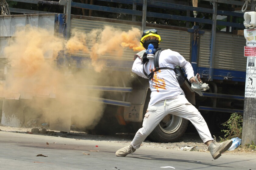 An anti-coup protester throws a smoke bomb against police crackdown at Thaketa township in Yangon, Myanmar, Saturday, March 27, 2021. The head of Myanmar's junta used the occasion of the country's Armed Forces Day to try to justify the overthrow of the elected government of Aung San Suu Kyi, as protesters marked the holiday by calling for even bigger demonstrations. (AP Photo)