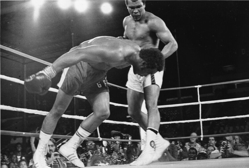 FILE - In this Oct. 30, 1974, file photo, challenger Muhammad Ali watches as defending world champion George Foreman goes down to the canvas in the eighth round of their WBA/WBC championship match in Kinshasa, Zaire. Ali, the magnificent heavyweight champion whose fast fists and irrepressible perso