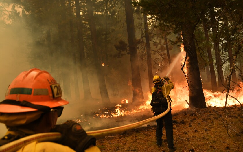 L.A. County firefighter Kevin Reid, right, and Capt. Donald Bailey battle the Caldor fire off Highway 89 west of Lake Tahoe.