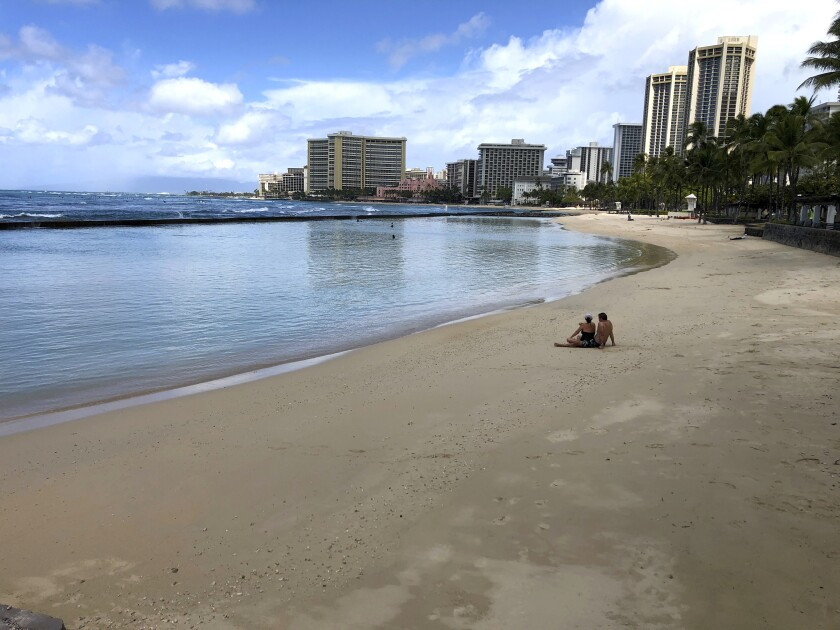 A couple sits on an empty section of Waikiki Beach in Honolulu in March.