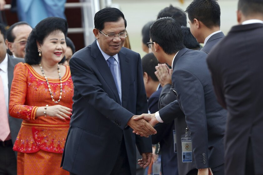 Cambodia's Prime Minister Hun Sen, center, and his wife Bun Rany, left, are greeted by officials on their arrival for the 27th Association of Southeast Asian Nations (ASEAN) summit, in Sepang, Malaysia, Friday, Nov. 20, 2015. (AP Photo/Lai Seng Sin)