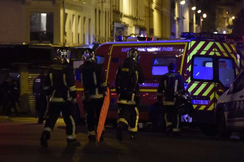 Police and other emergency workers secure the area following an attack at the Bataclan concert hall in central Paris on Friday.