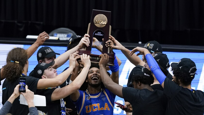 UCLA guard Tyger Campbell (10) celebrates with teammates after an Elite 8 game against Michigan in the NCAA men's college basketball tournament at Lucas Oil Stadium, Wednesday, March 31, 2021, in Indianapolis. UCLA won 51-49. (AP Photo/Darron Cummings)
