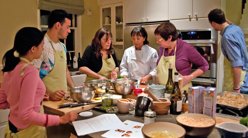Chef and instructor Miyoko Schinner (center, in white) gives tips to participants at her one–evening