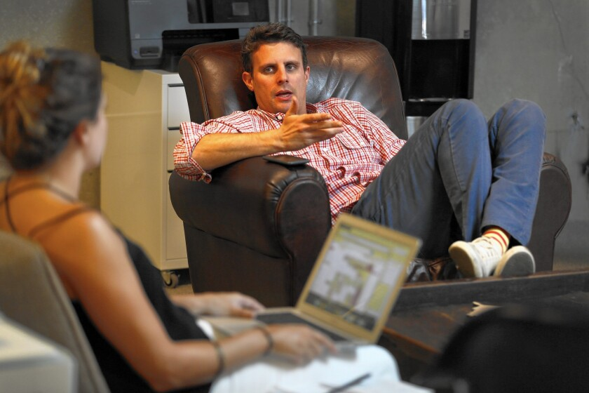 Dollar Shave Club chief Mike Dubin, center, talks with his assistant in his office. Dollar Shave Club has doubled its membership in less than 10 months.