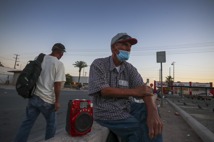 A 65-year-old man in a mask sits and waits for a day labor job in Calexico.