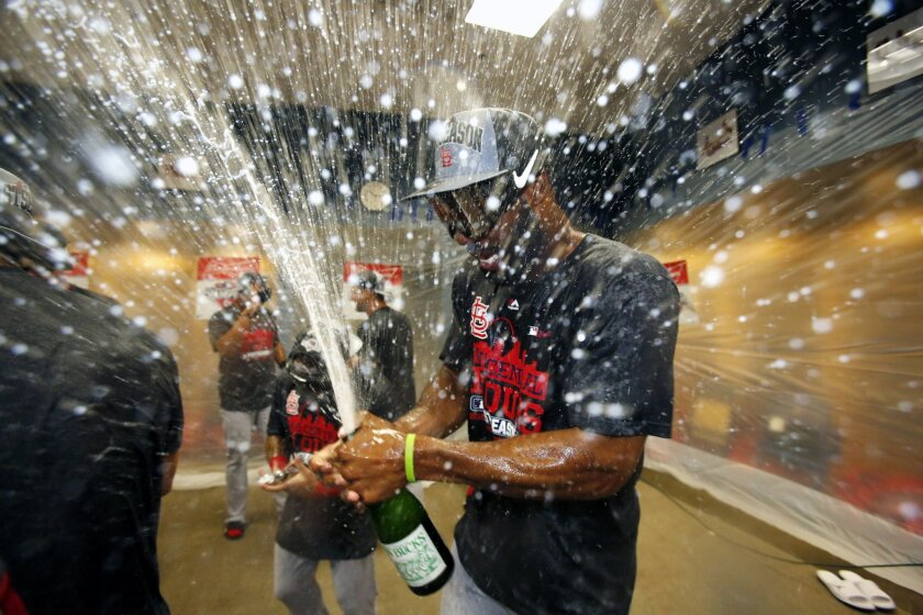 St. Louis Cardinals' Jason Heyward pops the cork on a bottle after the Cardinals clinched the Central Division with an 11-1 win over the Pittsburgh Pirates in a baseball game in Pittsburgh, Wednesday, Sept. 30, 2015. (AP Photo/Gene J. Puskar)
