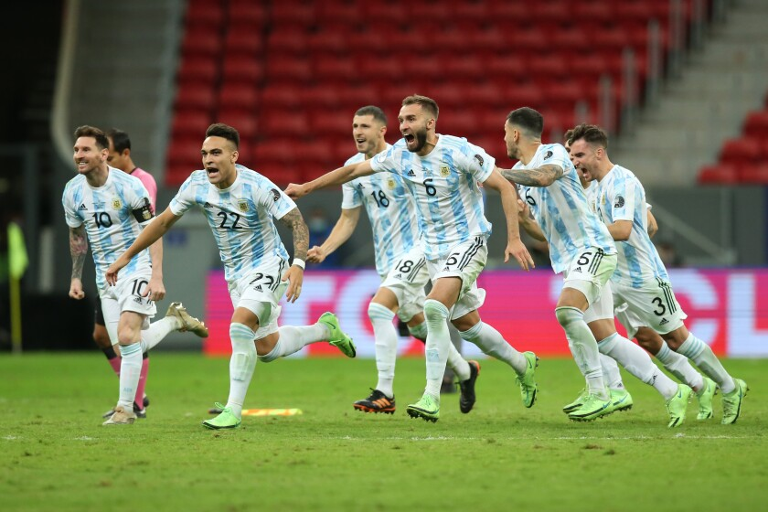 Argentine players celebrate with teammates after winning a penalty shootout