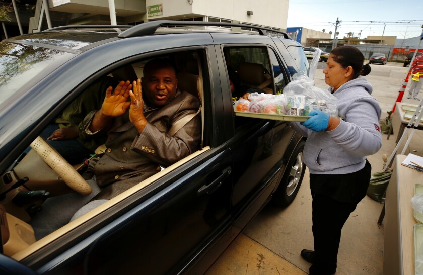 LOS ANGELES CA MARCH 18, 2020 -- Alake Ilegbameh said OMay God continue to bless youO over and over again as heOs driving his 3 school age children while he picks up food kits from LAUSD employee Benjula Prasad, right, being distributed to drivers in vehicles at Dorsey High School 3537 Farmdale Ave in Los Angeles Wednesday morning (Al Seib / Los Angeles Times)