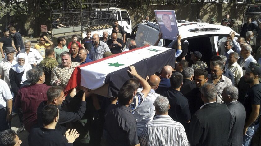 In this photo released by the Syrian official news agency SANA, mourners carry a coffin of more than