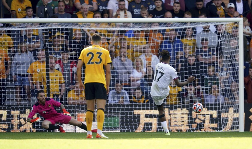 Brentford's Ivan Toney, right, scores the opening goal of the game against Wolverhampton Wanderers, during their English Premier League soccer match at Molineux Stadium in Wolverhampton, England, Saturday Sept. 18, 2021. (David Davies/PA via AP)