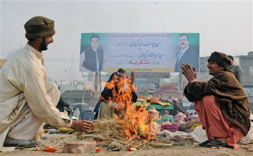 Backdropped by a billboard showing Pakistani Prime Minister Yousuf Raza Gilani, right, and his son Abdul Qadir, vendors gather around a fire to warm themselves, in Multan, Pakistan, Thursday, Jan. 6, 2010. Pakistan's prime minister says his government will reverse unpopular fuel price hikes that helped spark the break-up of the governing coalition. (AP Photo/Khalid Tanveer)