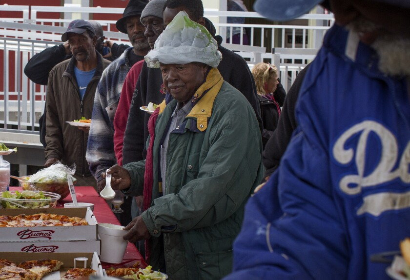 Residents of a new shelter in Watts receive plates full of pasta, pizza and salad during a Christmas Lunch held on Monday.