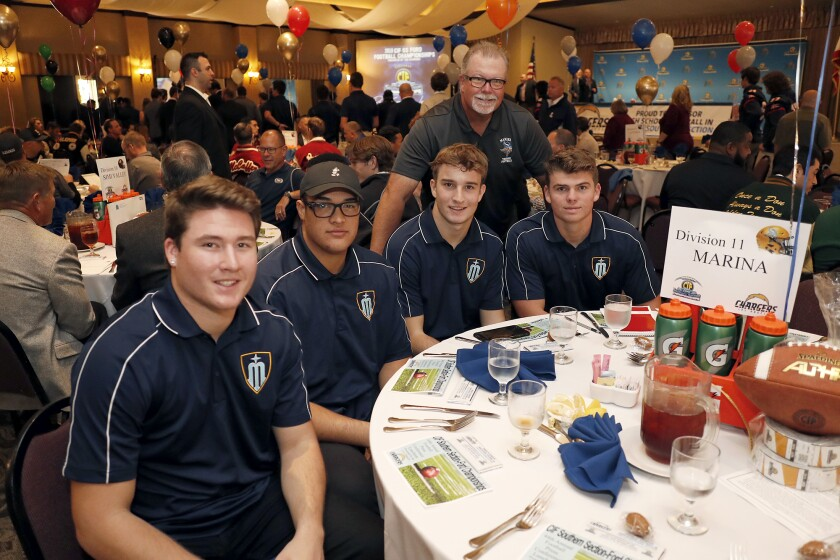 Marina coach Jeff Turley, standing, and players Nathan O'Rourke, left, Isaia Regan, Eric Church and Chase Hoglund attend the CIF Southern Section football championship luncheon on Monday at the Grand in Long Beach.