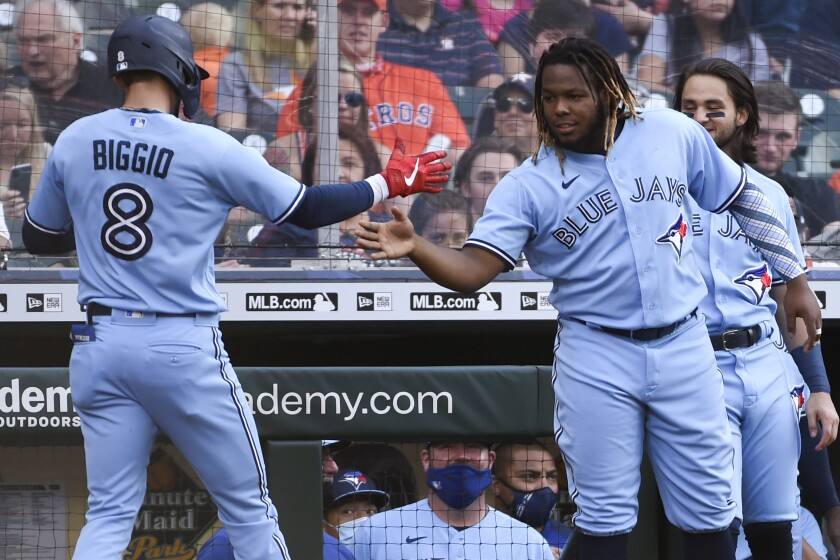 Toronto Blue Jays' Cavan Biggio (8) celebrates with Vladimir Guerrero Jr. as Biggo returns to the dugout after hitting a two-run home run during the second inning of the team's baseball game against the Houston Astros, Saturday, May 8, 2021, in Houston. (AP Photo/Eric Christian Smith)